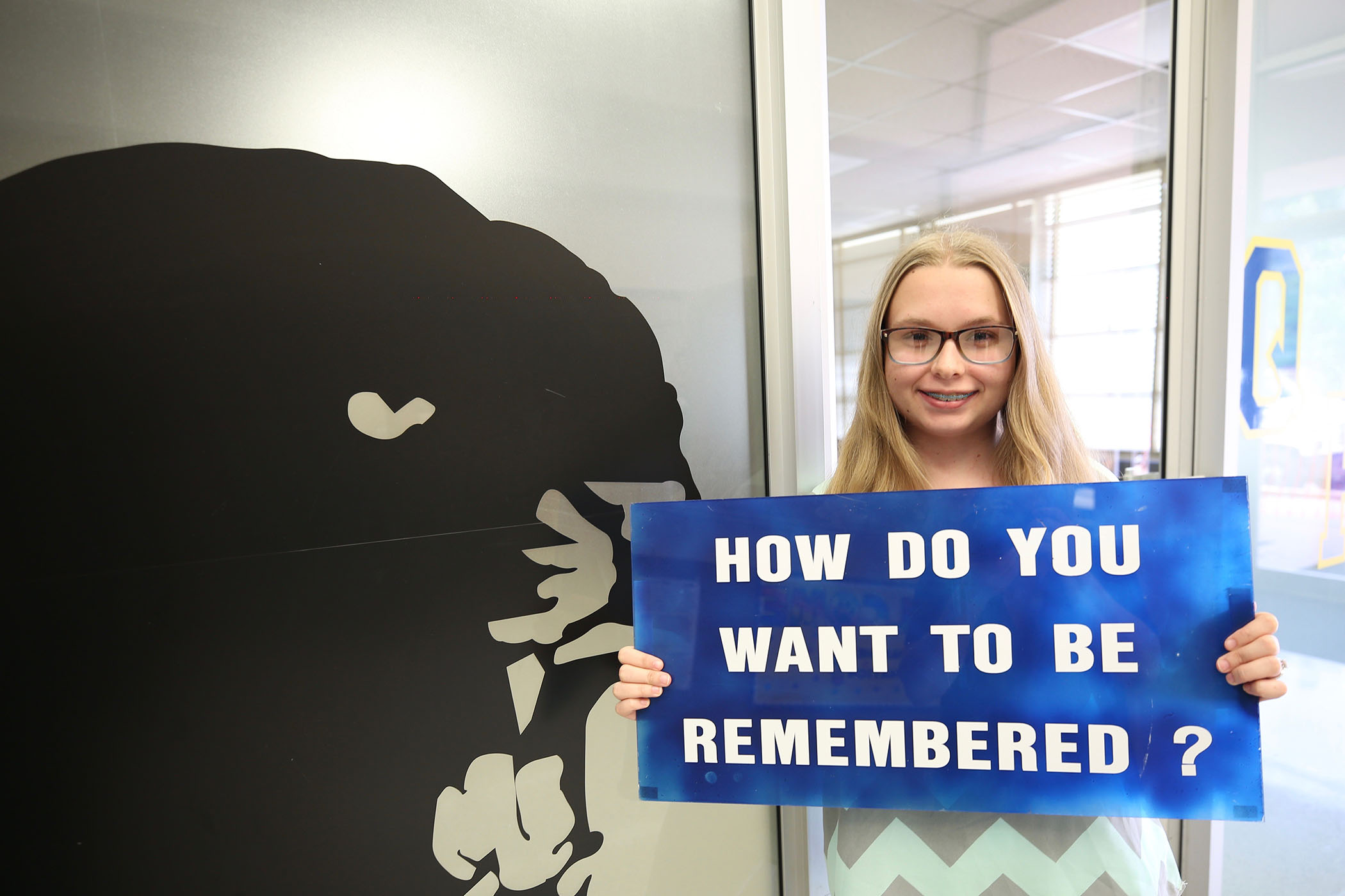 """Madison stands with a familiar sign. """"How do you want to be remembered?"""" is written on it."""