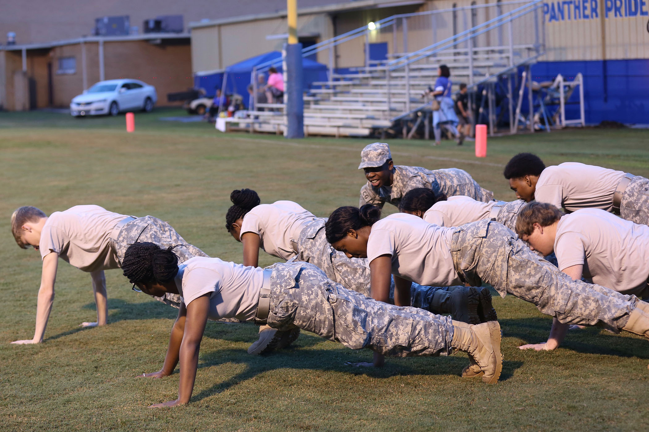 Panther JROTC do pushups on Panther Field after a touchdown.