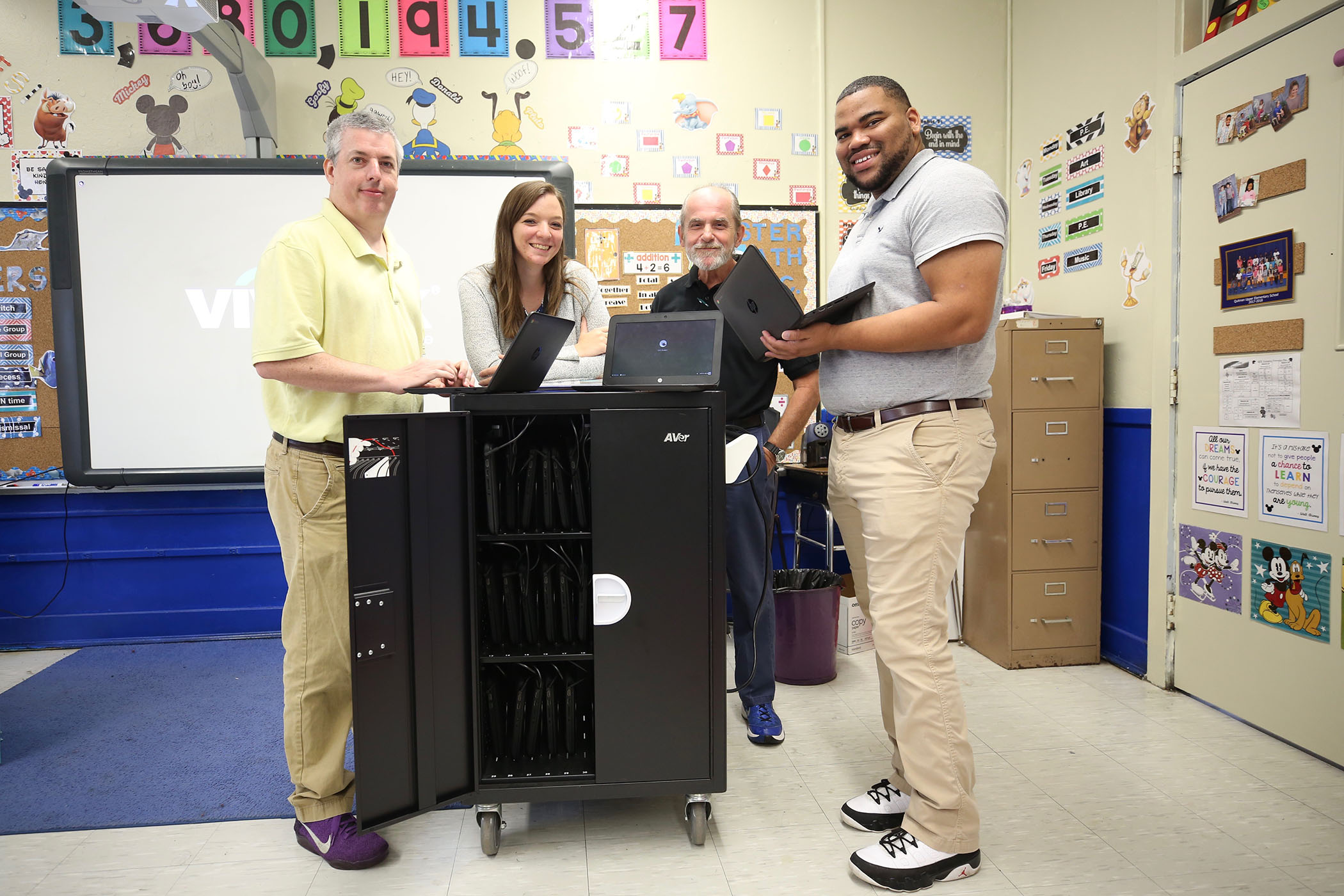 A teacher and the QSD Tech Department poses with the classroom's Chromebooks.