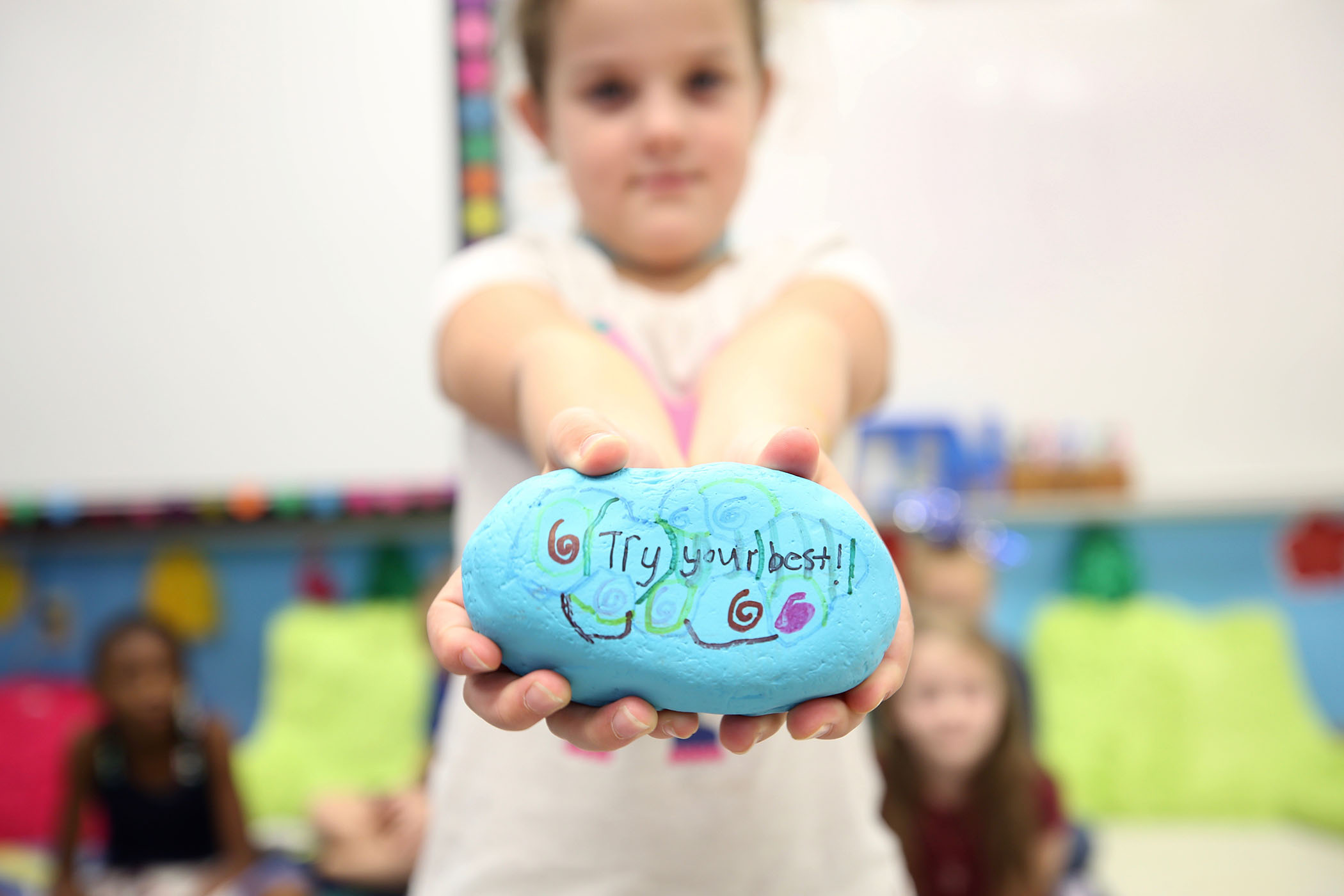 "A 2nd grade student stands with a kindness rock she painted. On it is written, ""Try your best."""