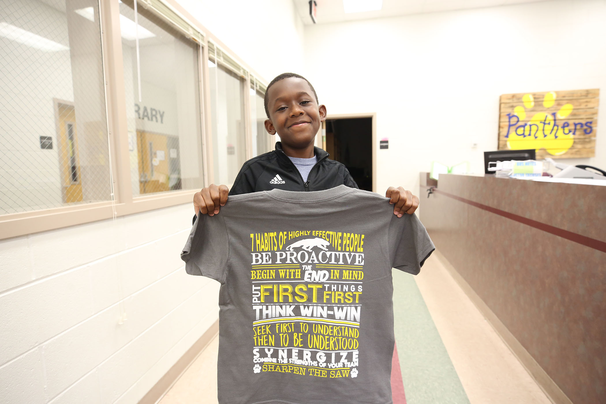 QJH student poses with community read t-shirt.