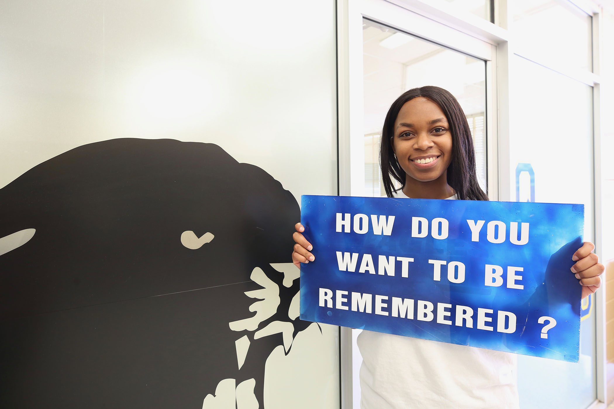 "Carlondria poses with a sign which reads, ""How do you want to be remembered?"""