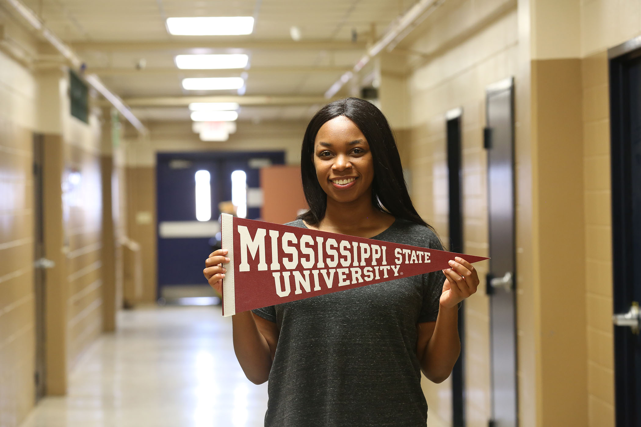 Carlondria poses with a Mississippi State University banner.