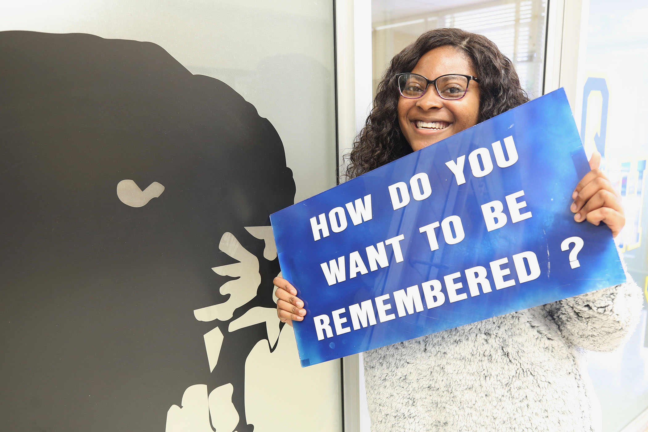 "Ellie poses with a sign which reads, ""How do you want to be remembered""?"""