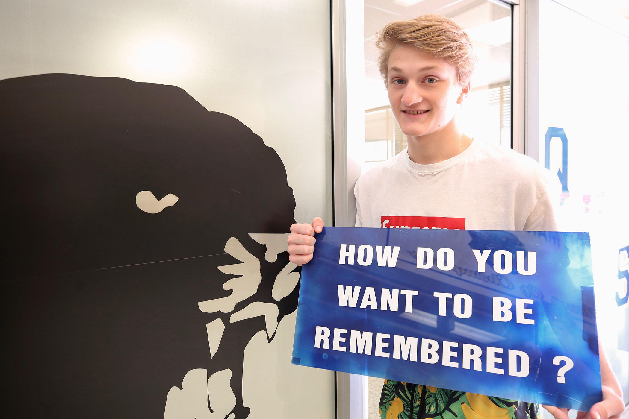 "Jayce stands with a sign which reads, ""How do you want to be remembered?"""