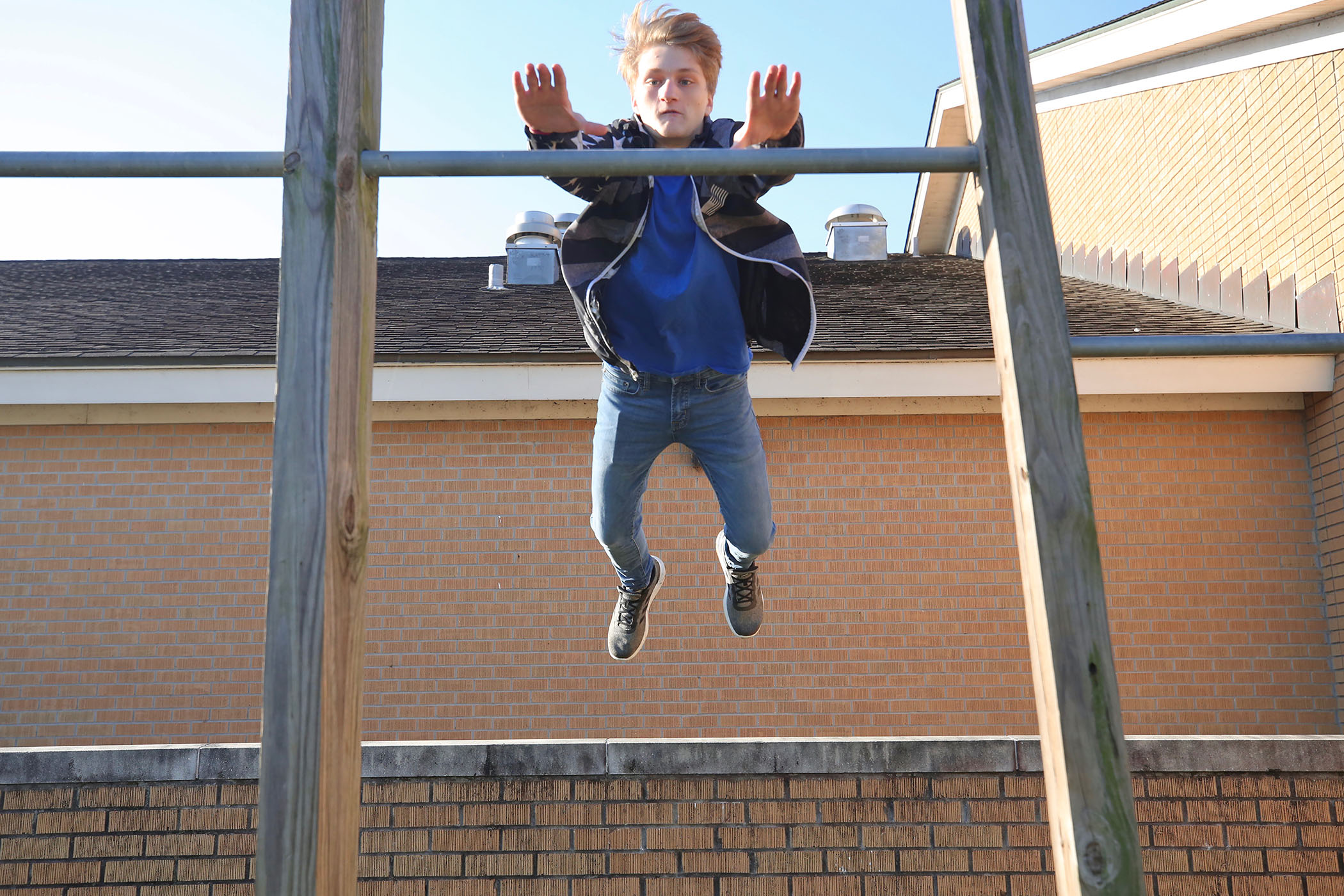 Jayce leaps from the brick wall next to the QHS Library.