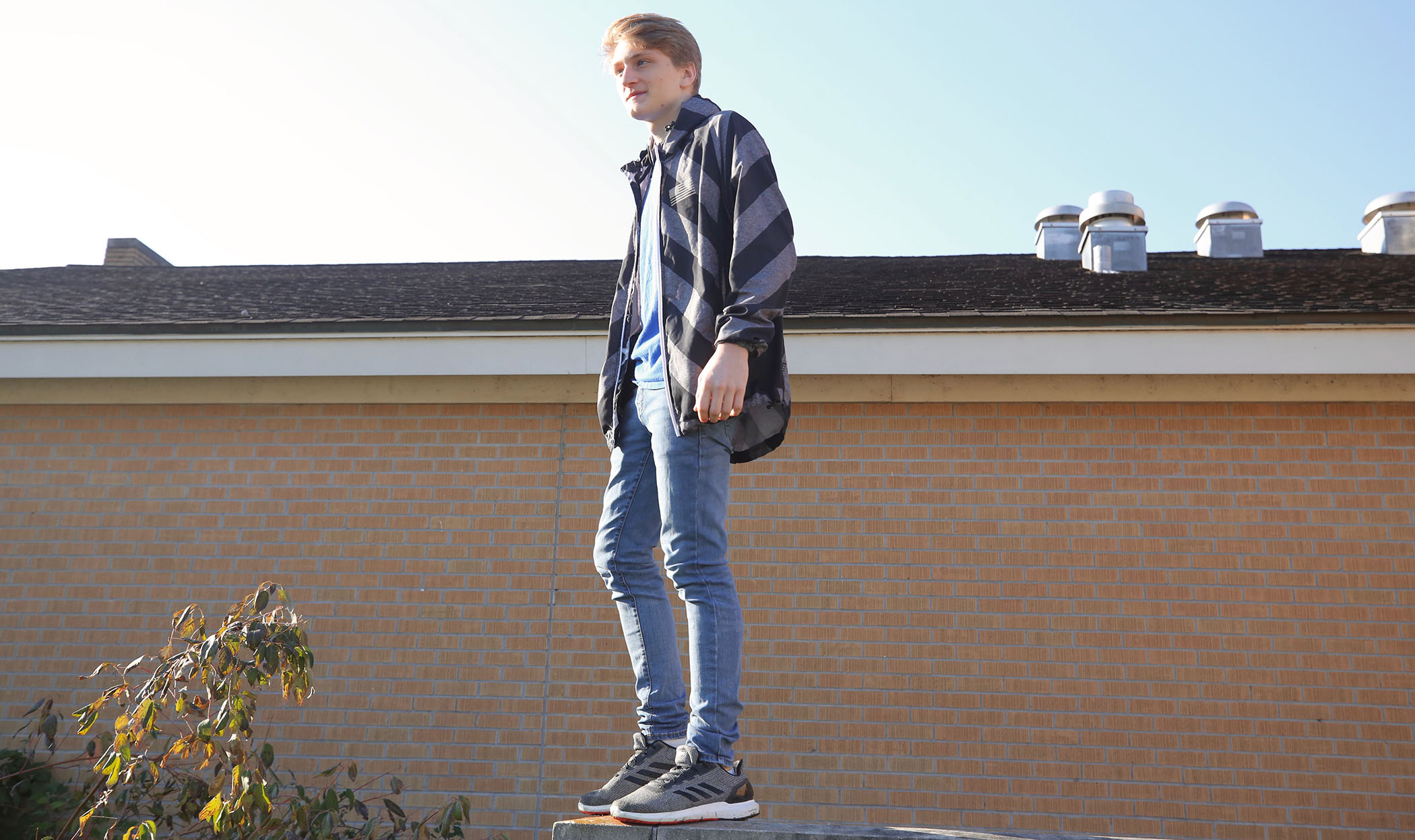 Jayce stands on a brick wall next to the QHS Library.
