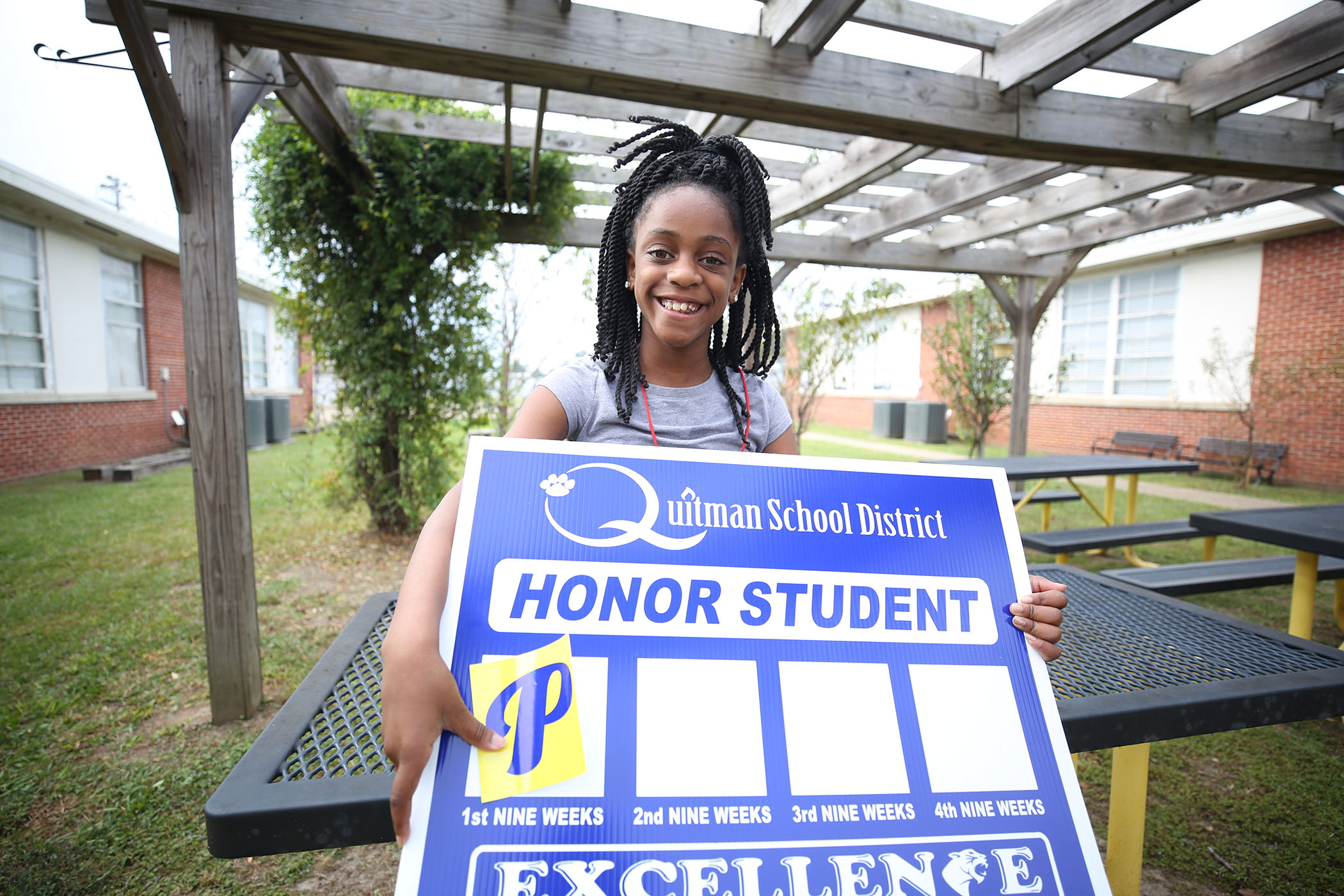 A QUE student holds her honor student yard sign.