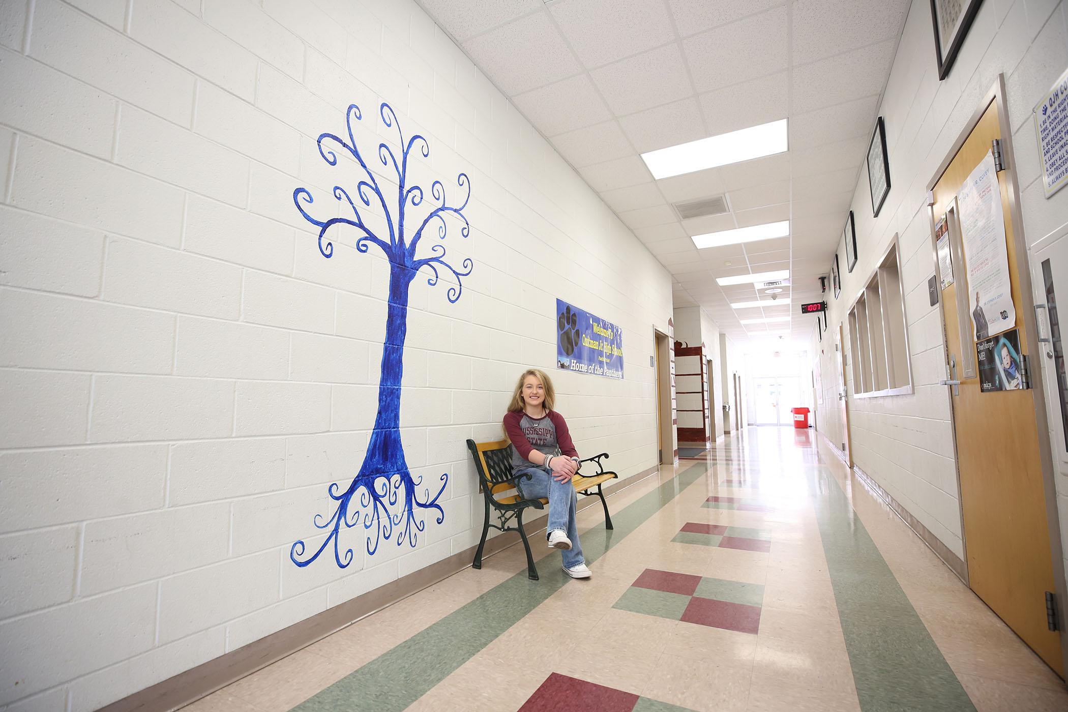 QJH student sits near mural.