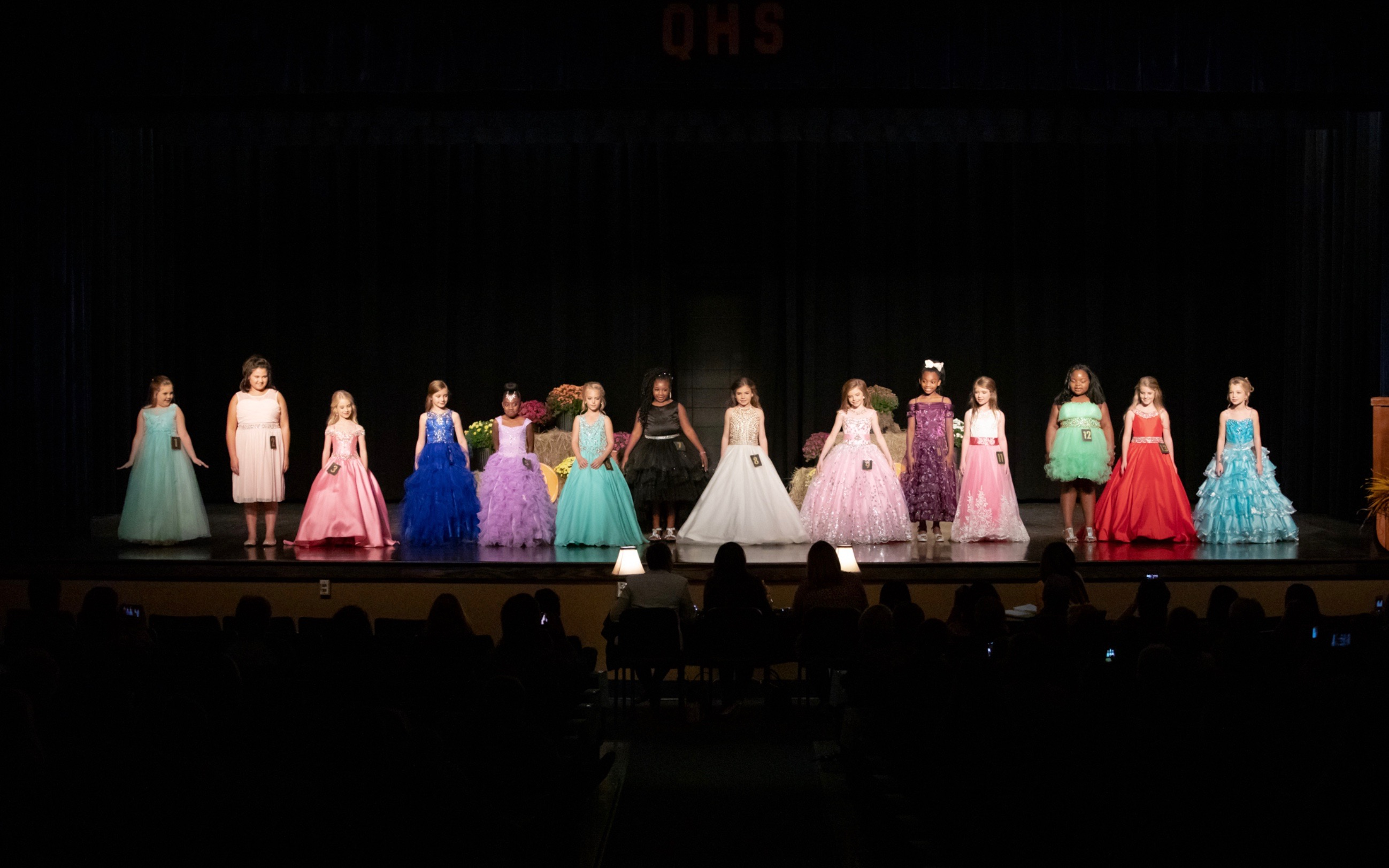 Pageant contestants pose on stage in QHS Auditorium.