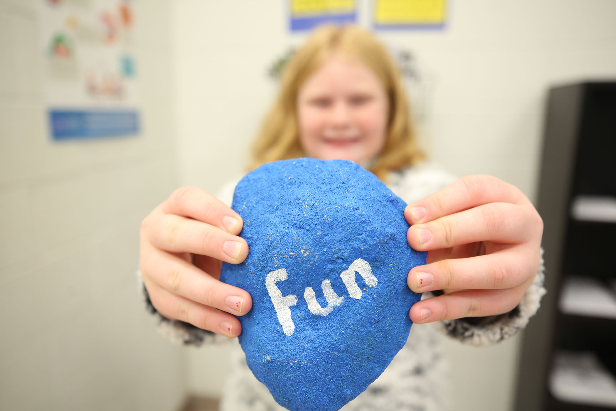 "A student holds up a big rock which has the word ""Fun"" painted on it."