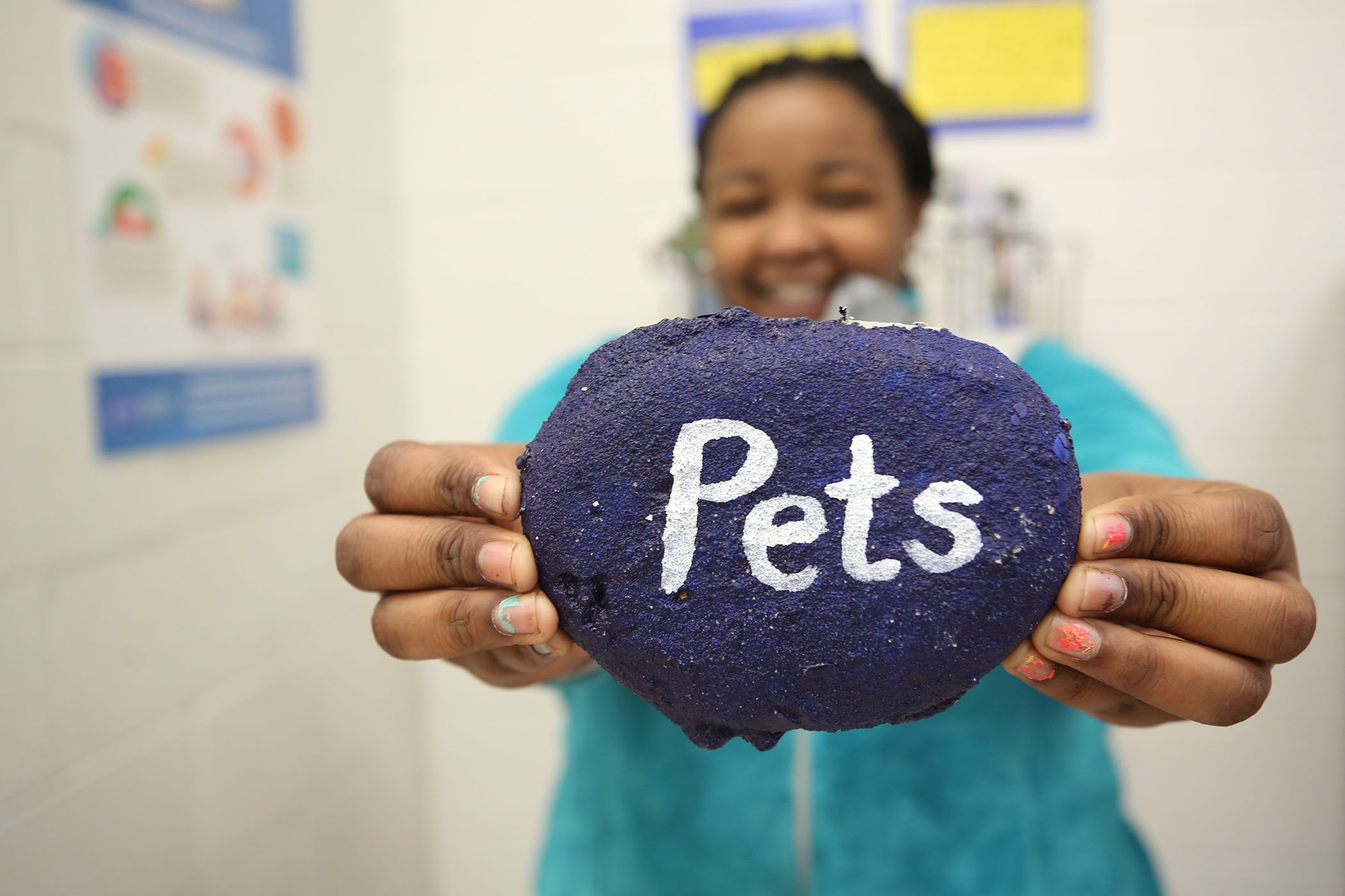 "A QJH student holds up a rock which has ""Pets"" painted on it."