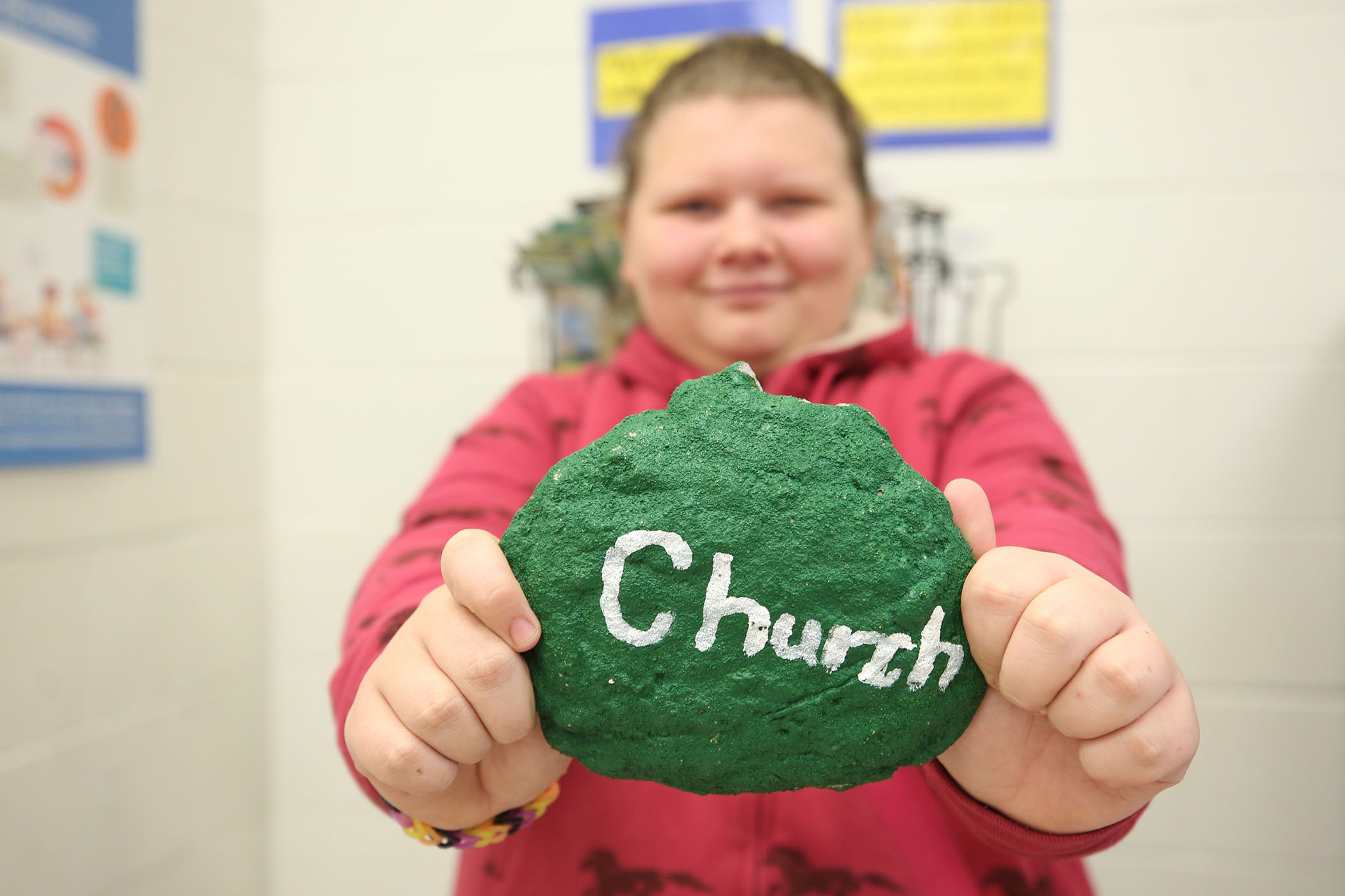 "A QJH student holds up a rock which has ""Church"" painted on it."