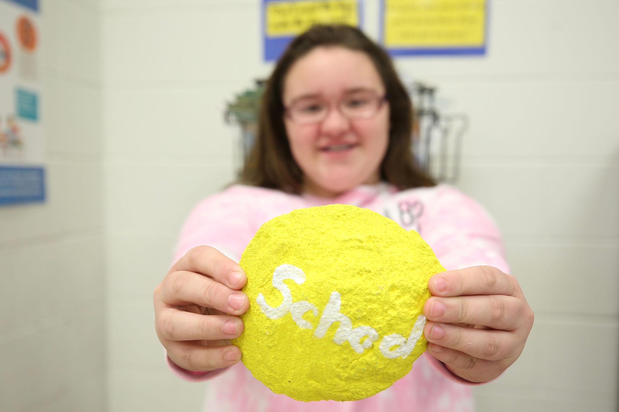 "A QJH student holds a rock which has ""School"" painted on it."