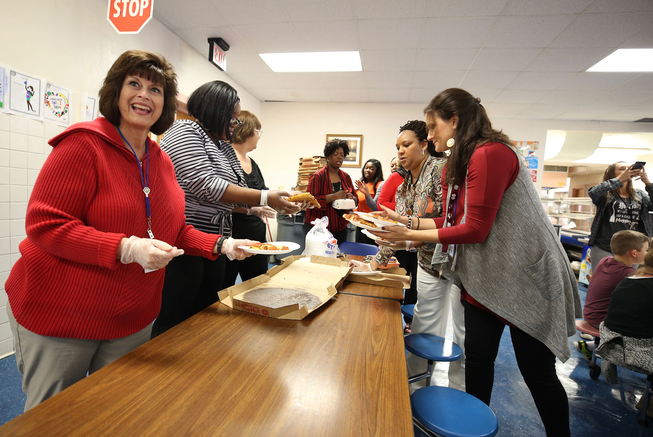 Central office staff serve pizza to students.