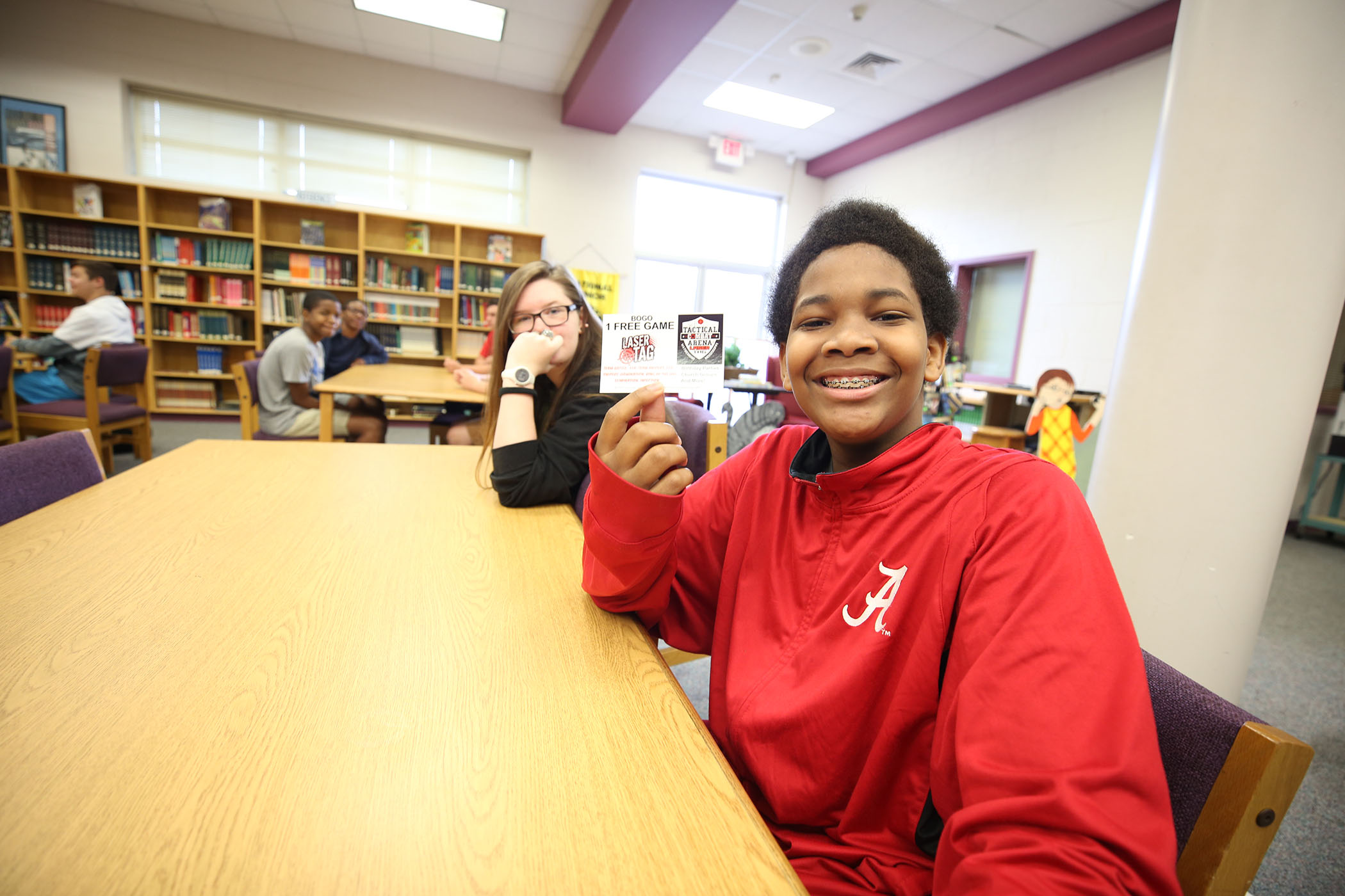 QJH student holds up a free laser tag card.