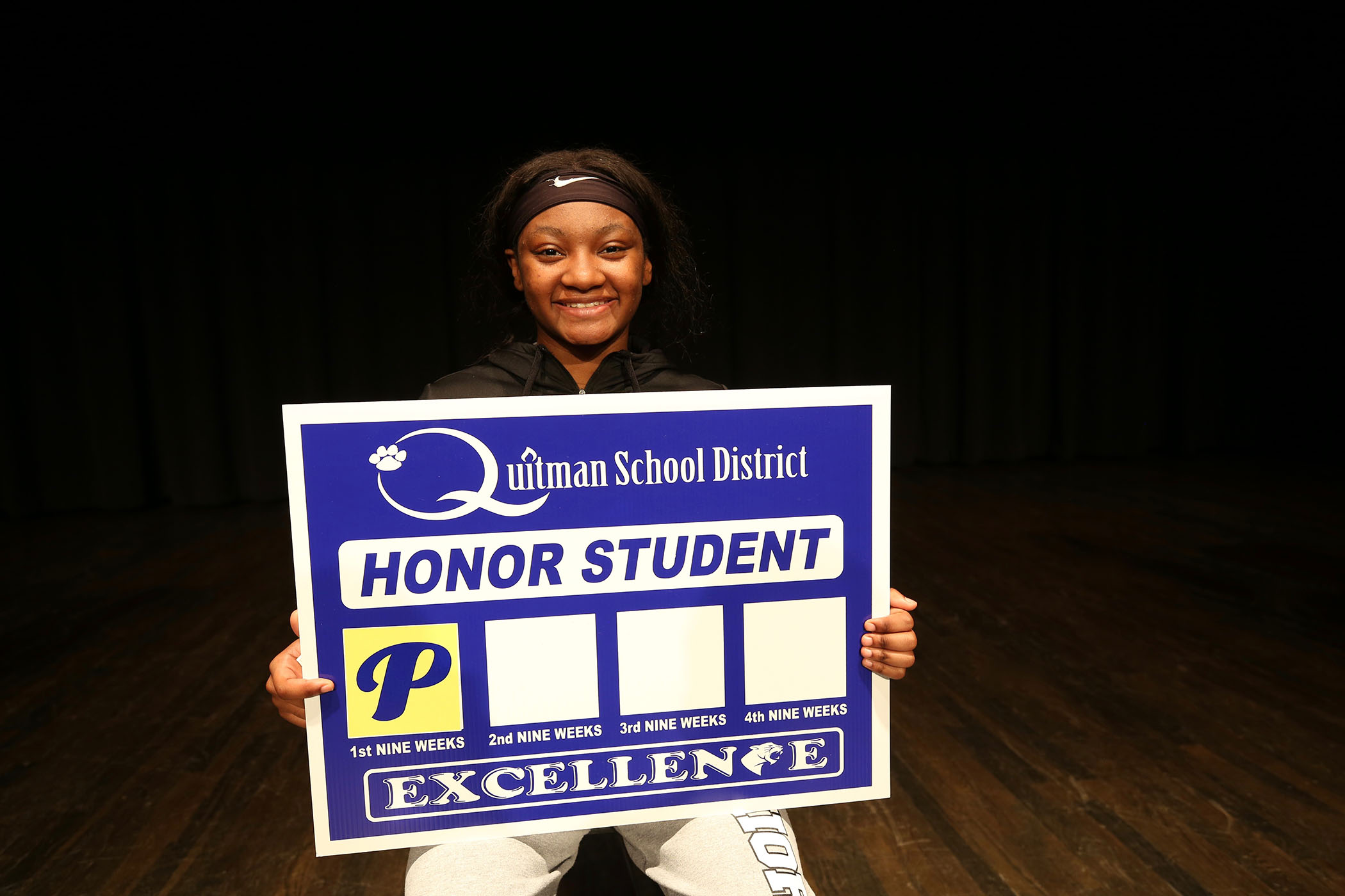 Raven holds a yard sign which announces that she is an honor student.