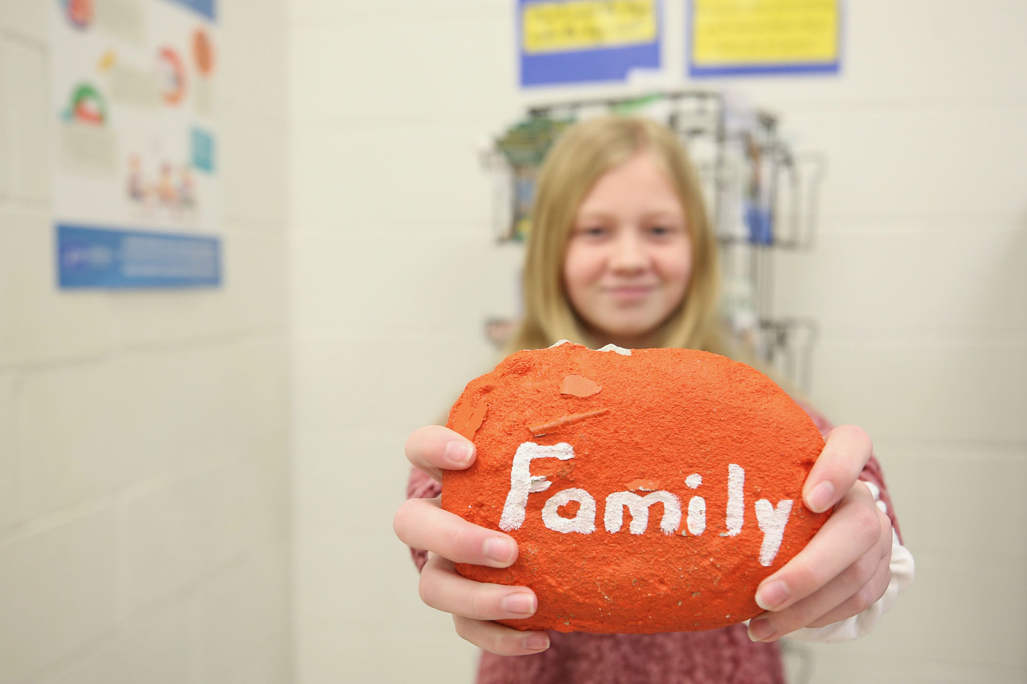 A QJH student holds up a rock painted with the word family.