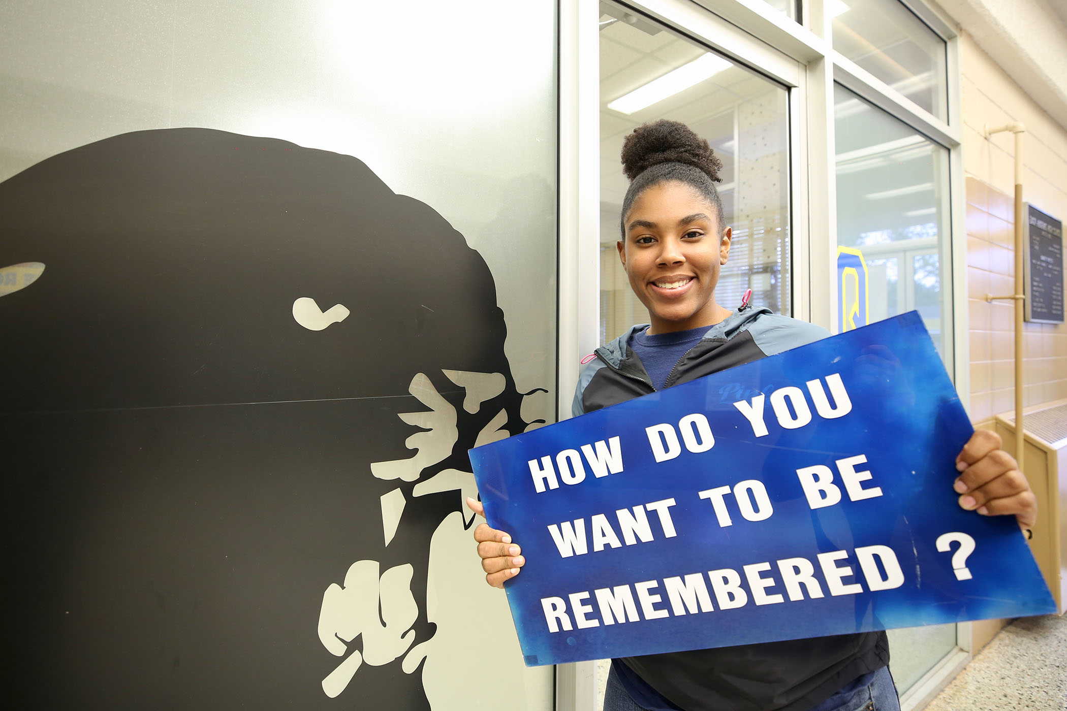 """Sayjah poses with a sign which asks, """"How do you want to be remembered?"""""""