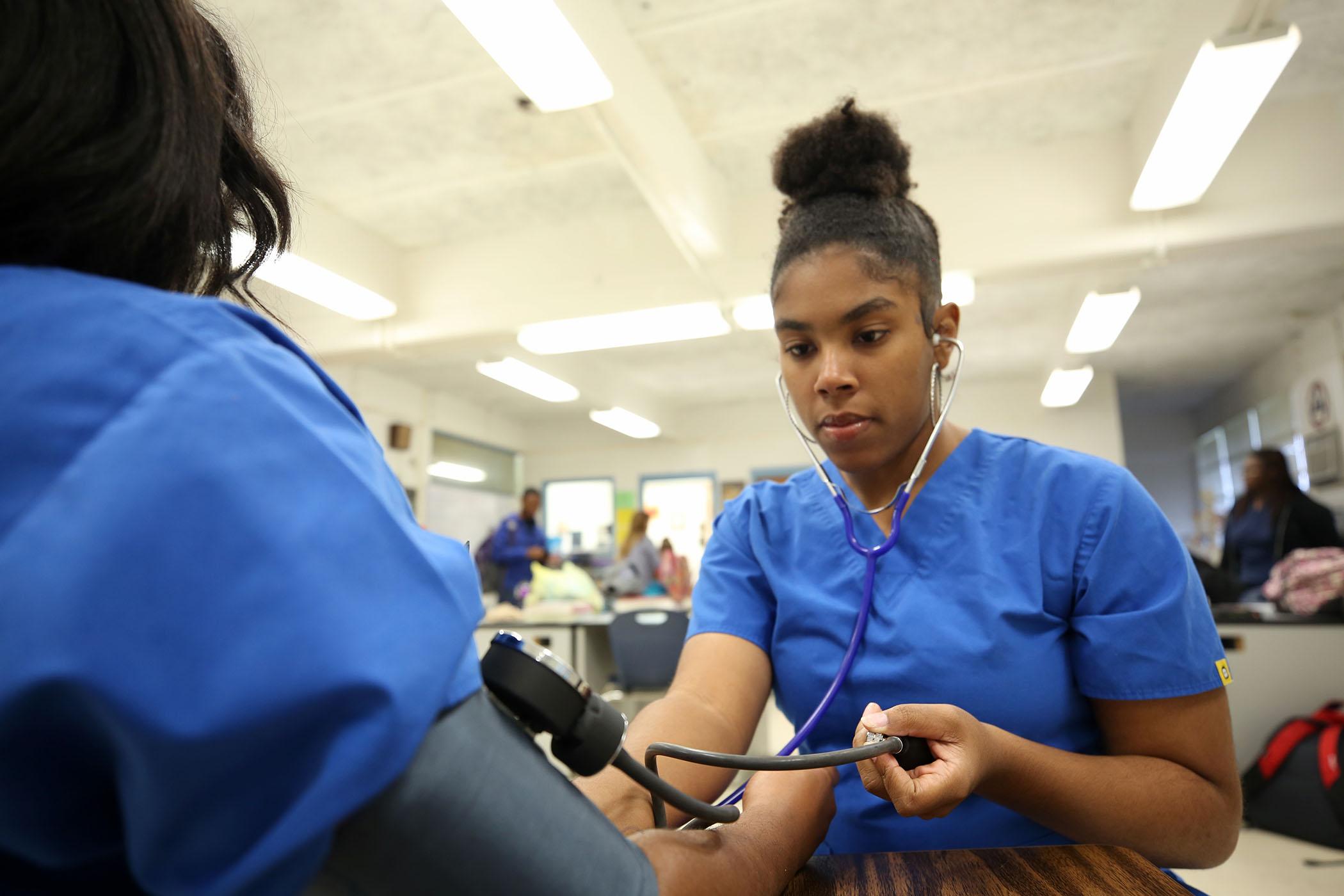 Sayjah checks a classmate's blood pressure during Health Science II.
