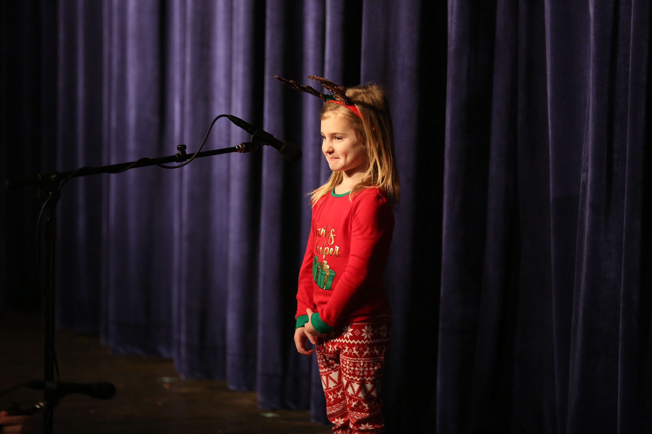 A QLE student introduces the Christmas program to the audience of fellow students.