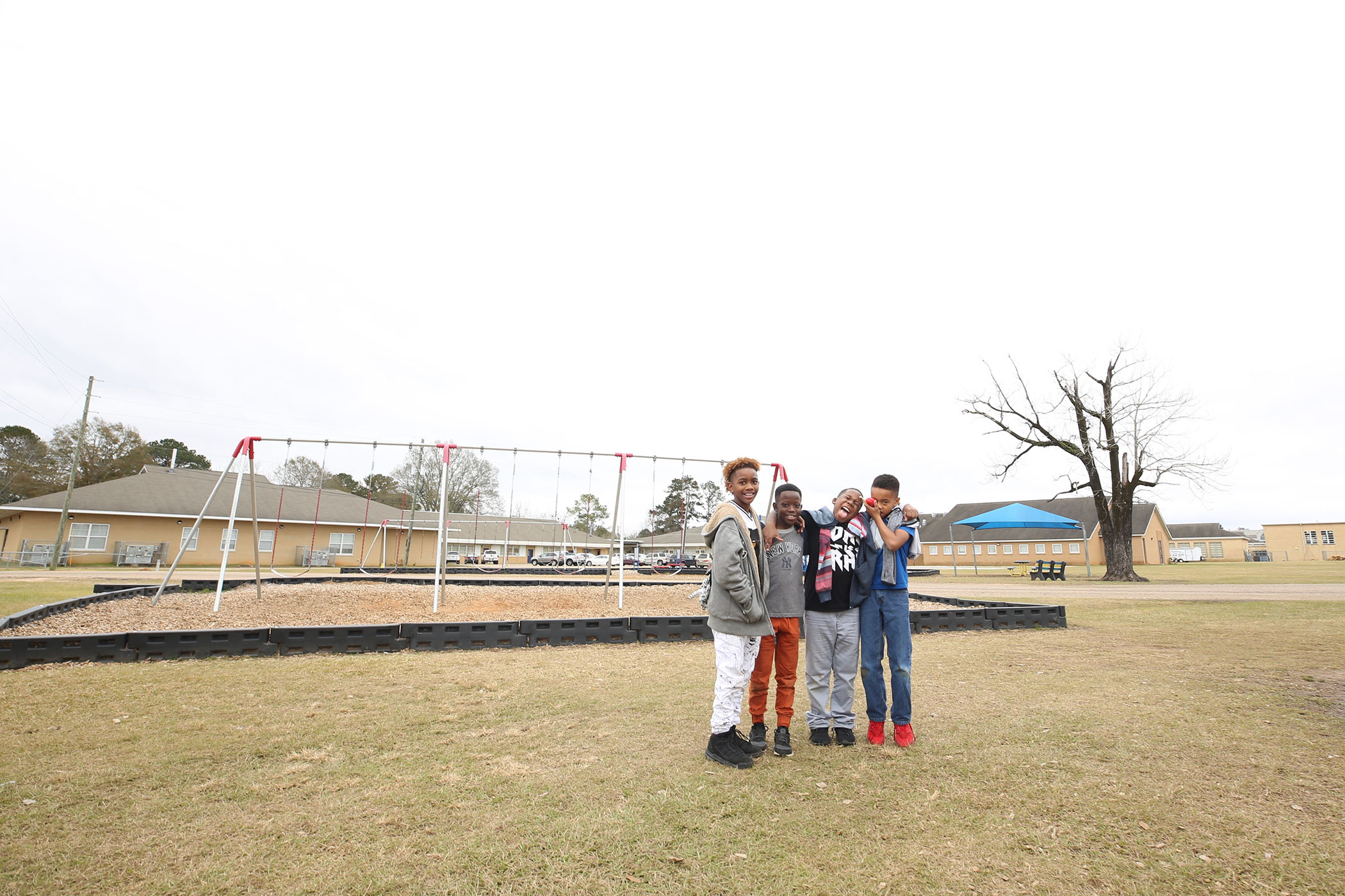 QUE students stand proudly on the playground they volunteered to clean.