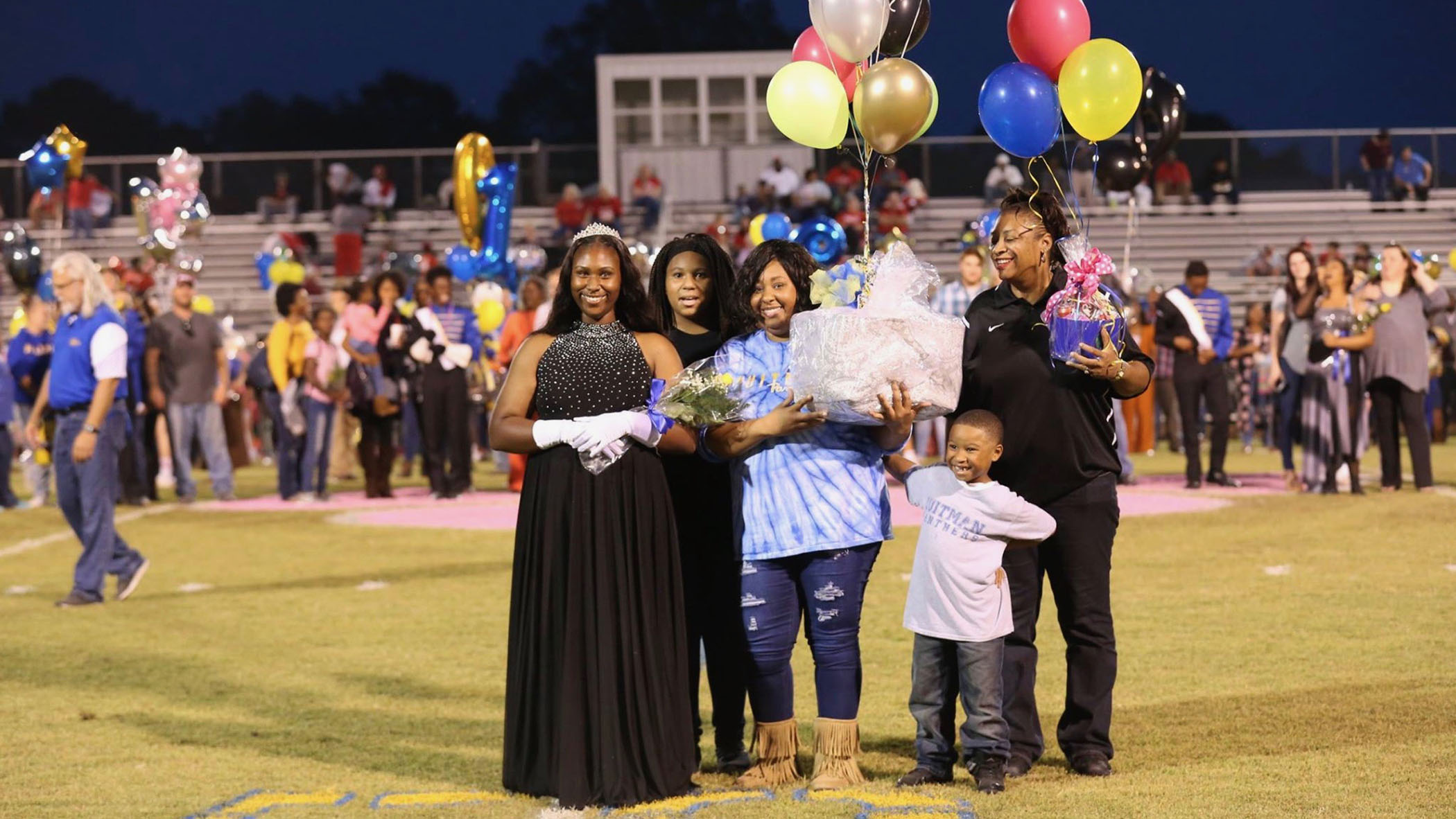 Takia walks out onto Panther Field with her family.