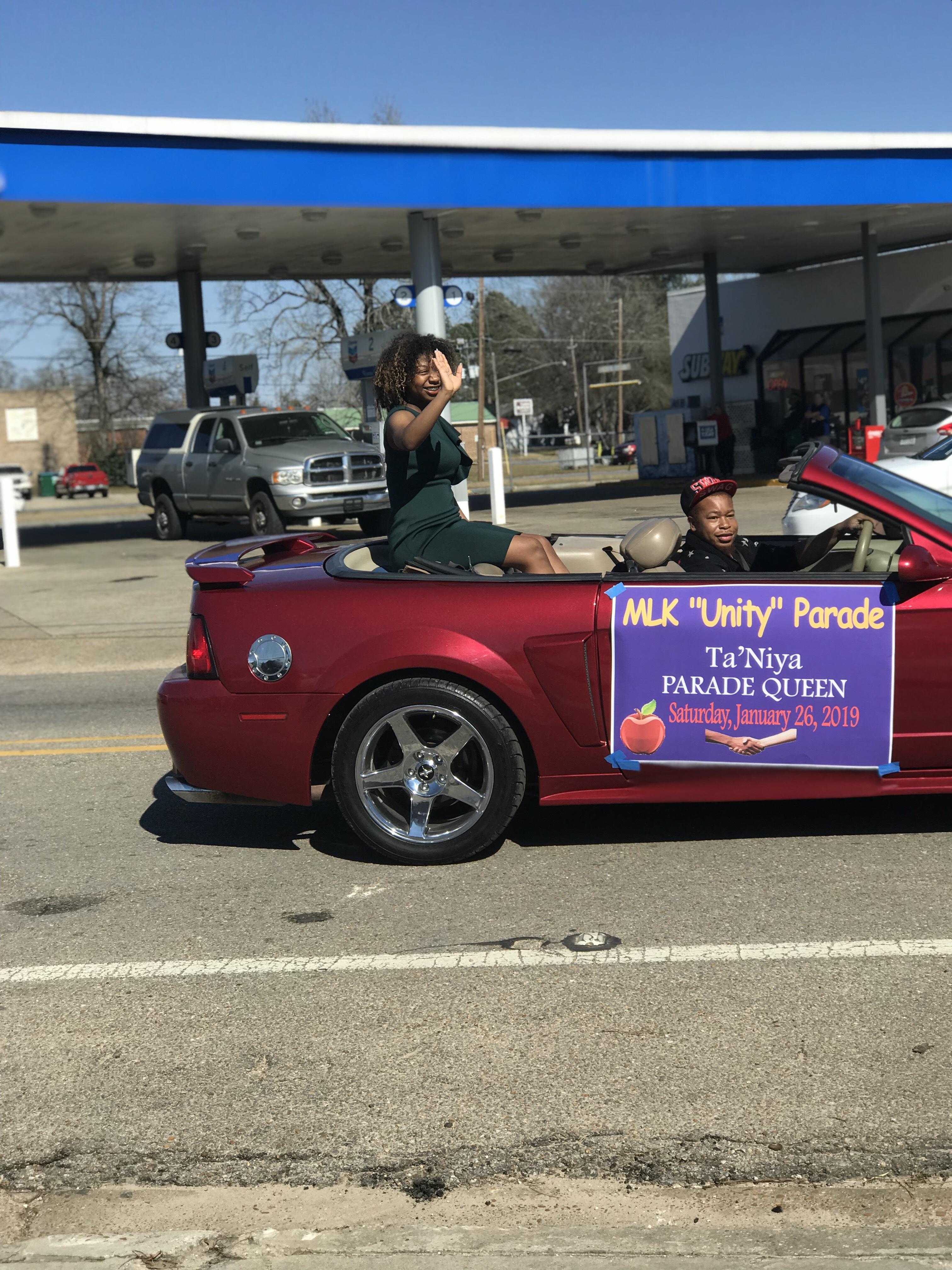 The MLK Parade Queen rides in a convertible.