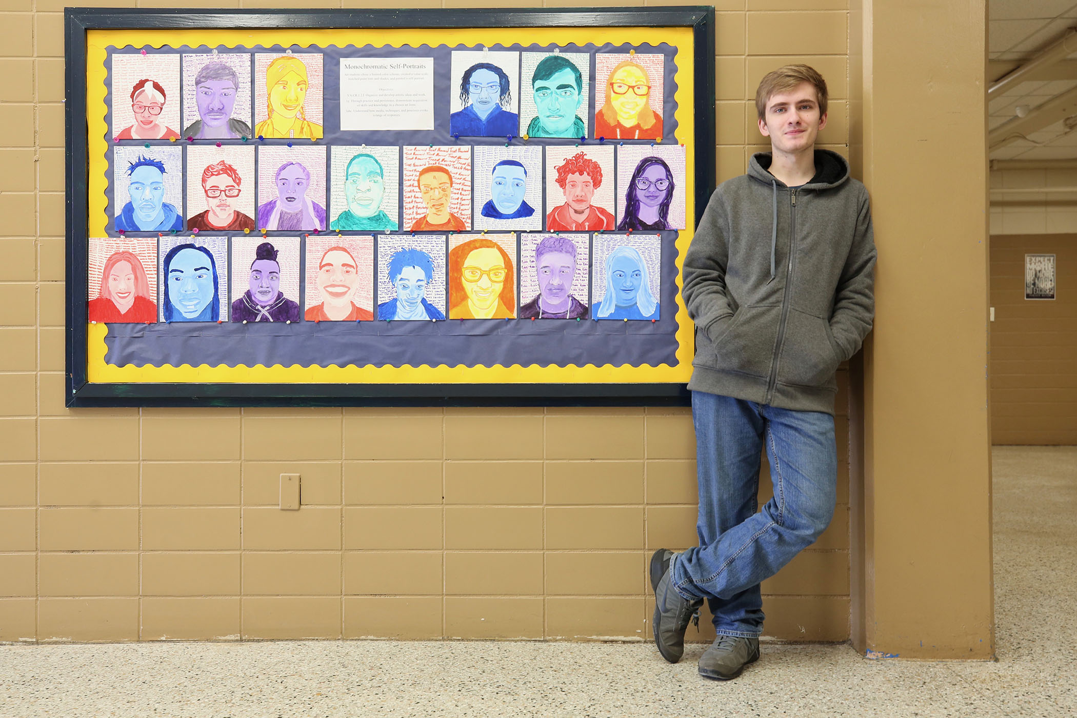 Brandon stands next to his self portrait.