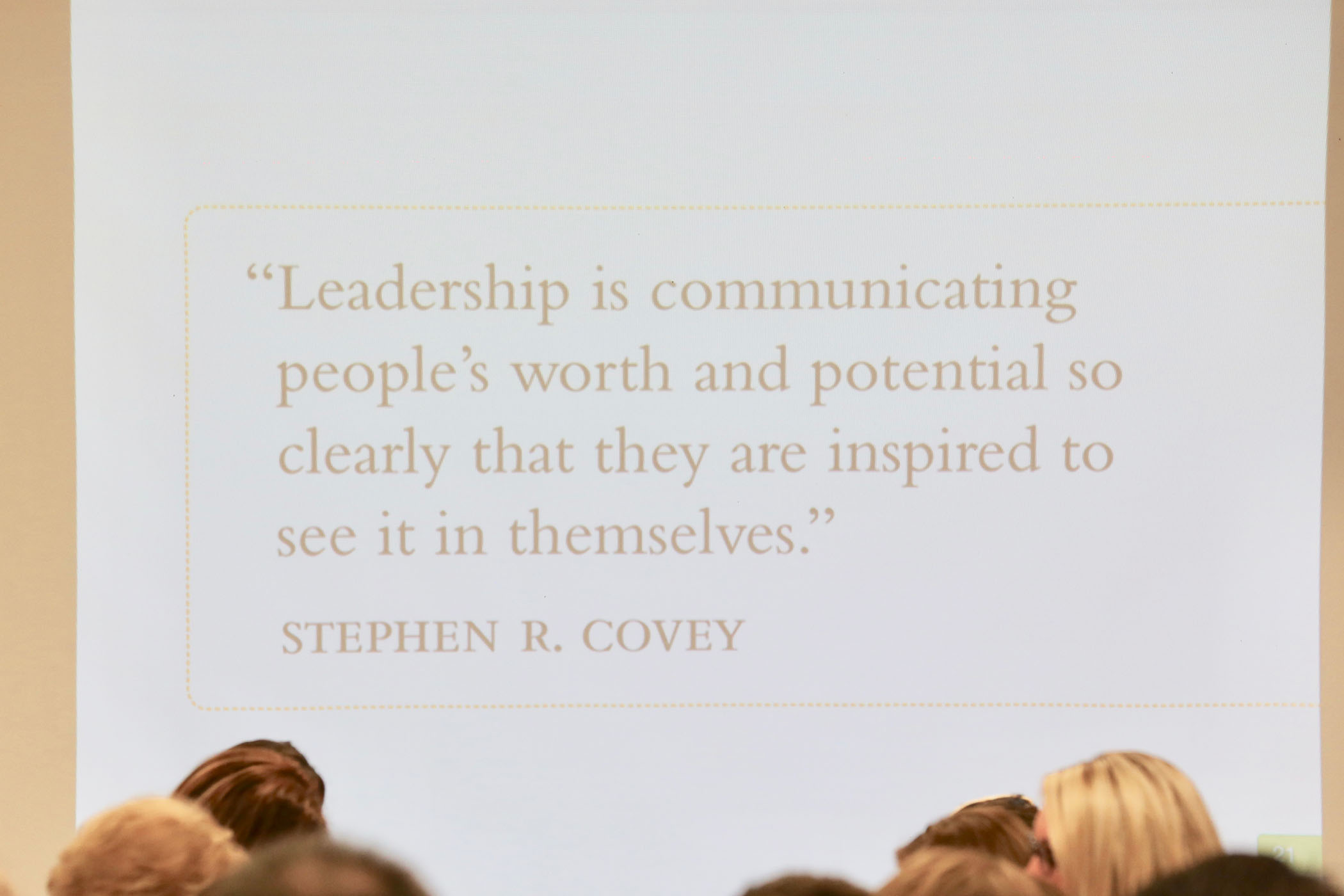 "A Powerpoint presentation slide displays a quote from Stephen R. Covey. ""Leadership is communicating people's worth and potential so clearly that they are inspired to see it in themselves."""