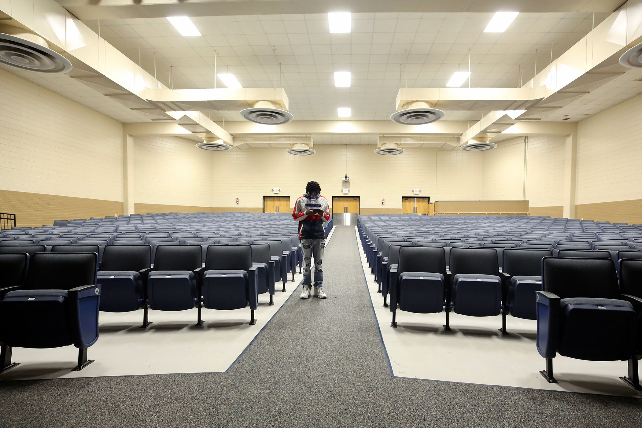 Panther Photography Club president Javante Charles waits in the QHS Auditorium for club members.