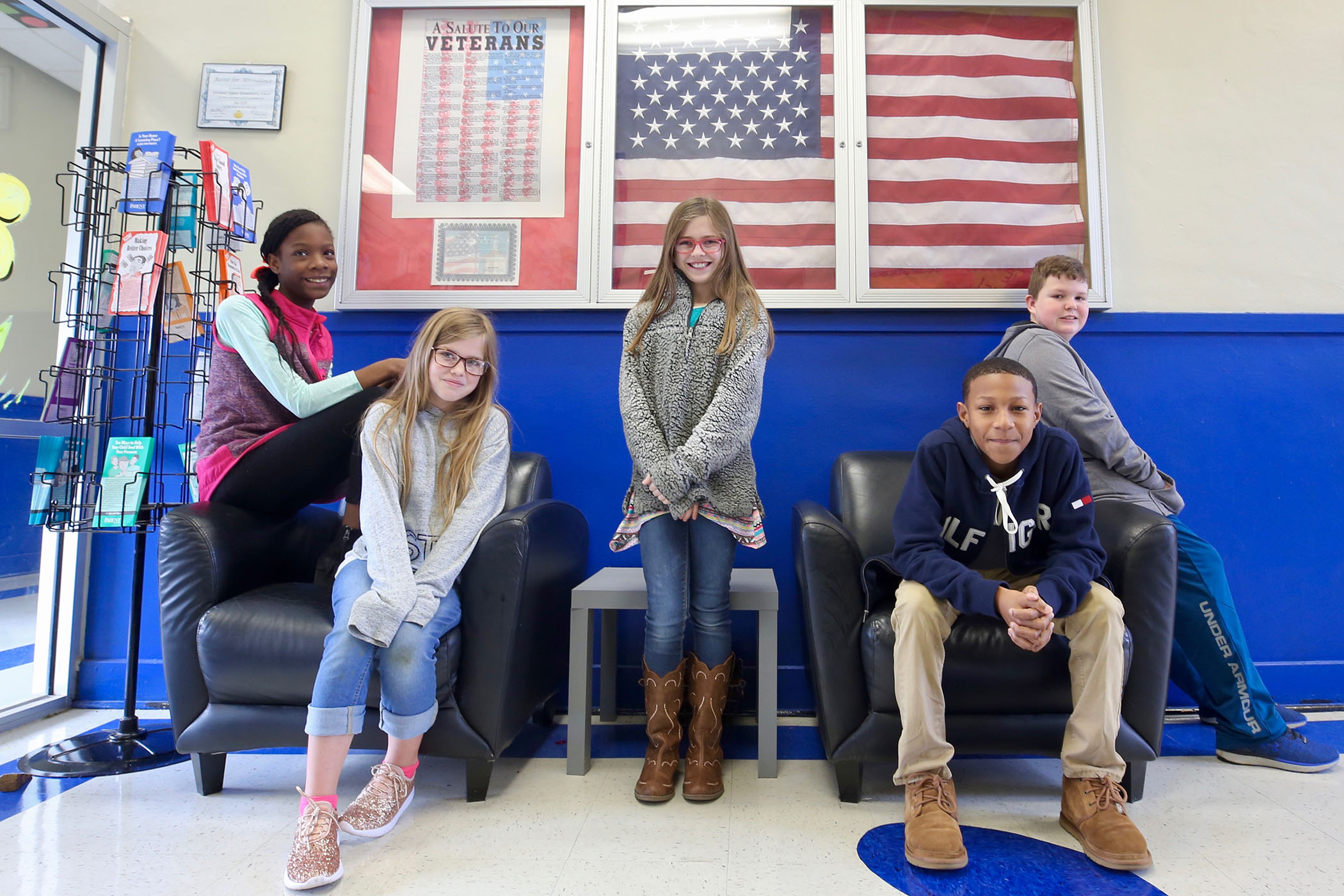 A group of QUE students are leading the school in the Pledge of Allegiance.