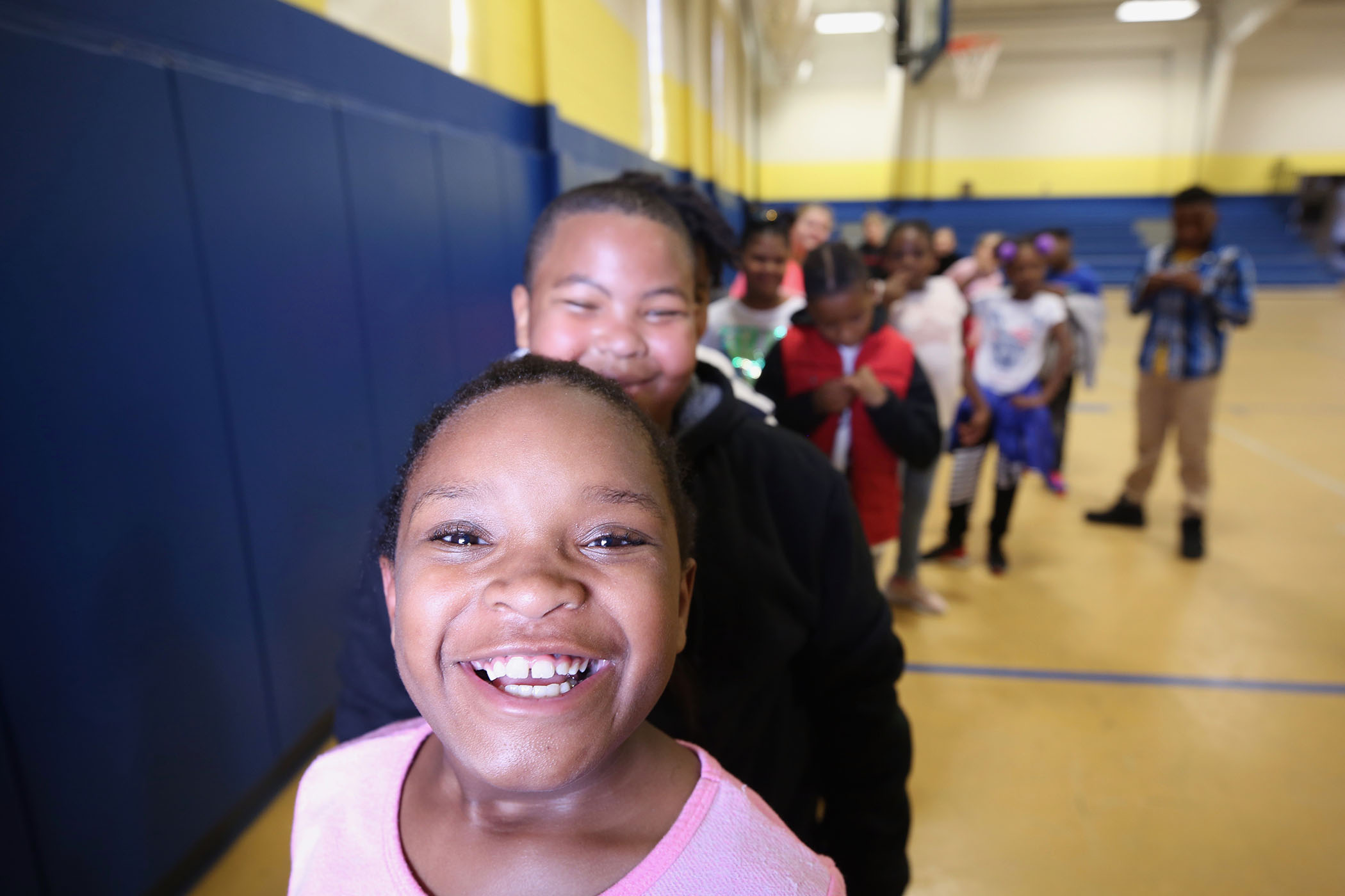 Students line up after enjoying a break in the school's gym.