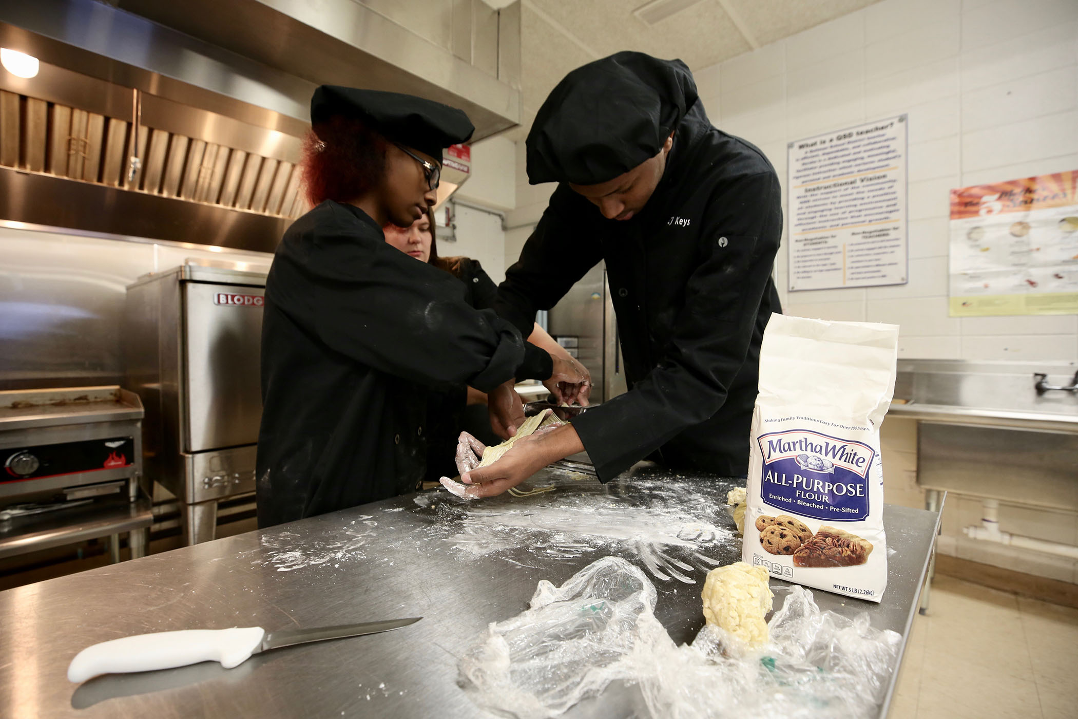 Culinary students make pasta.