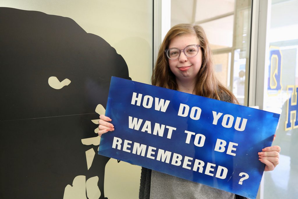 "Allie stands with a sign which reads, ""How do you want to be remembered?"""