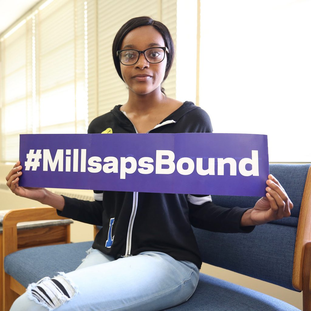 Allie poses with sign which reads #MillsapsBound.