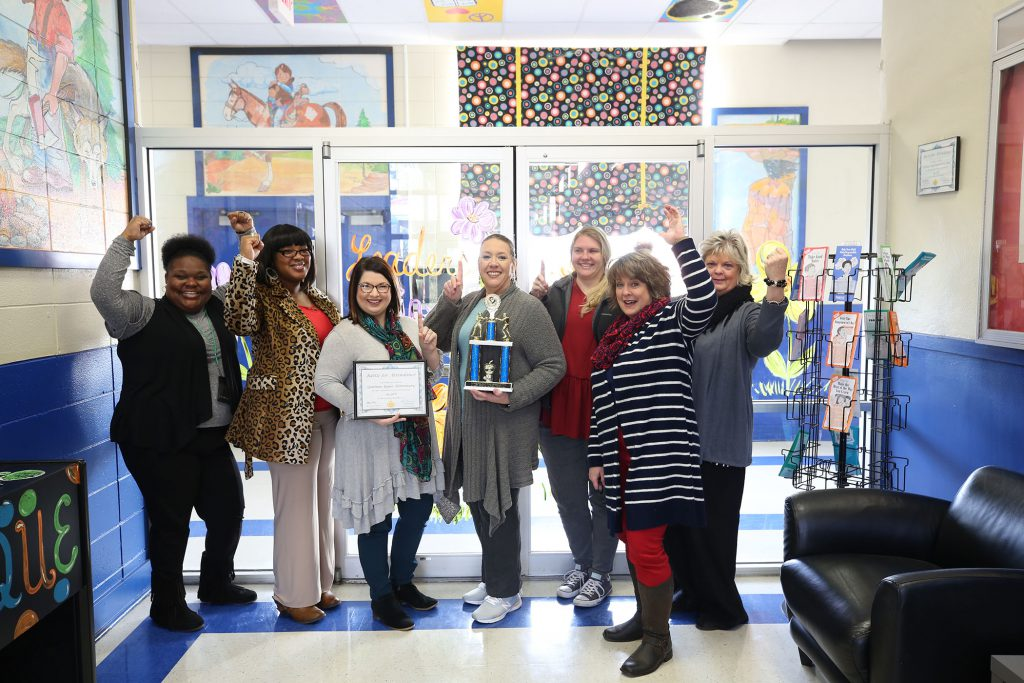 Leah poses with fellow staff for QUE's fourth consecutive attendance award.
