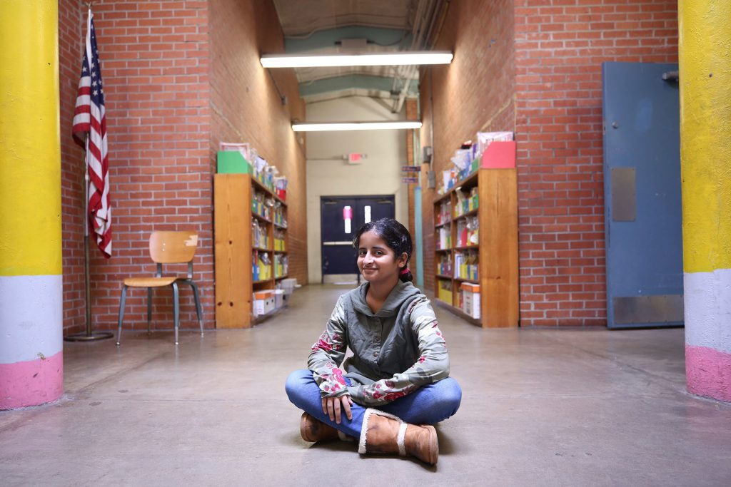 Rabab sits outside the library at QUE.