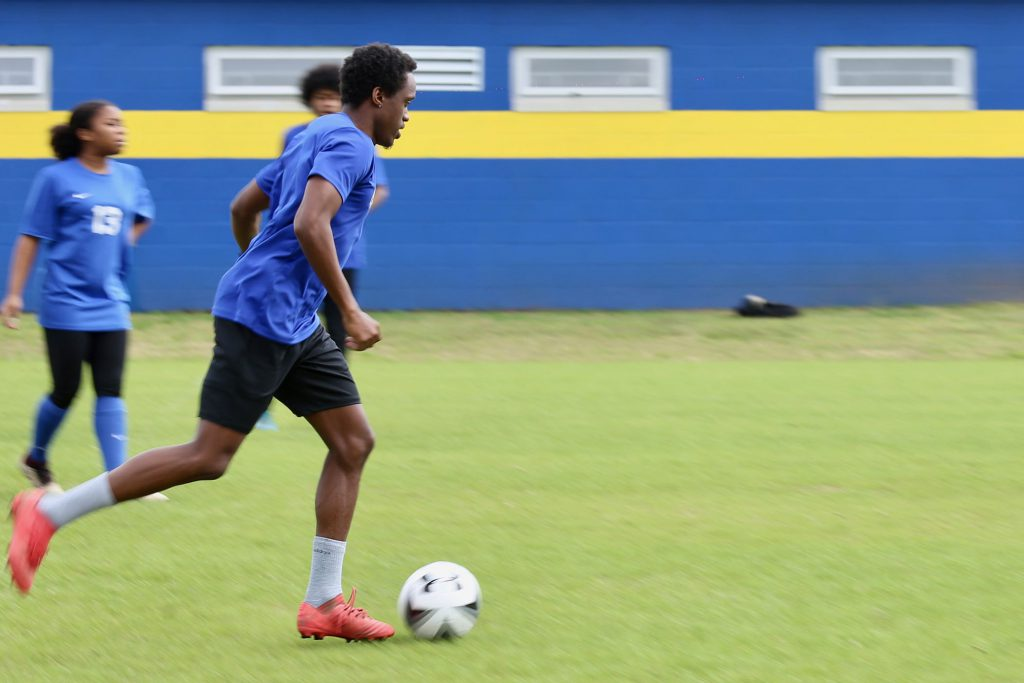 QHS Assistant Soccer coach Julio Noel gets some action shots for an article in the Meridian Star.