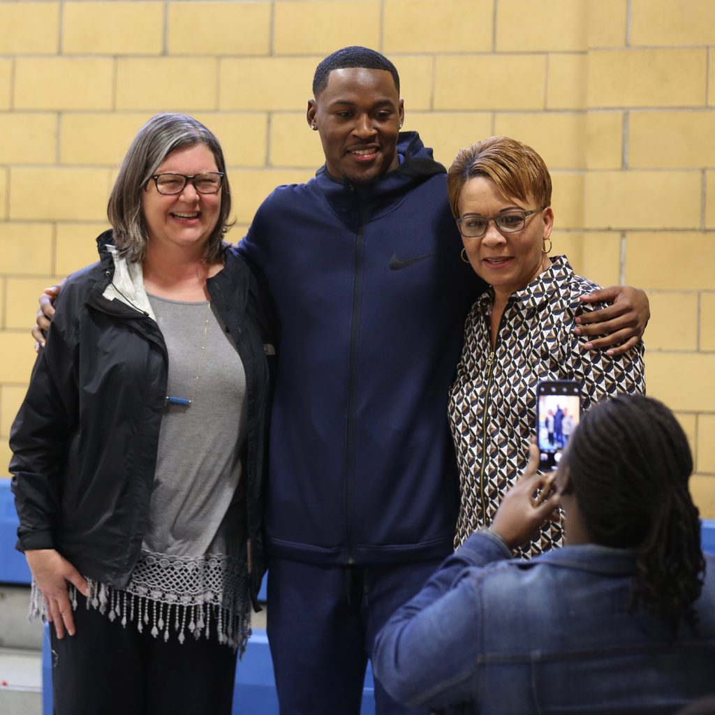 Tarvarius poses with two of his high school teachers.