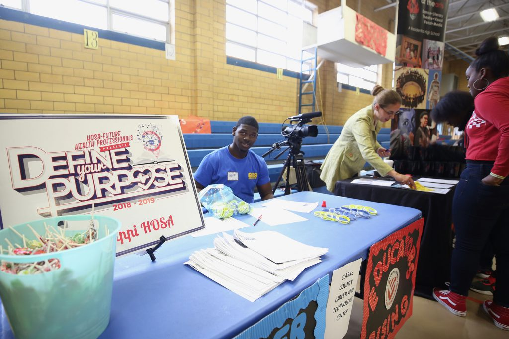 A student from the Clarke County Career Tech Center sits at a career fair booth.