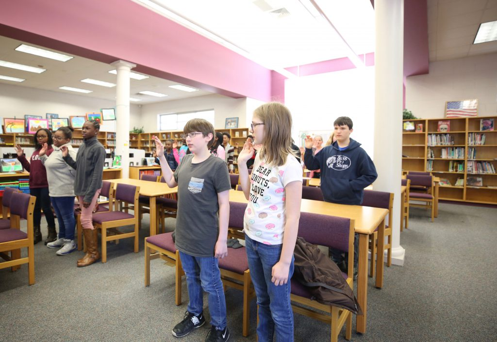 QJH Beta students are inducted in the library.