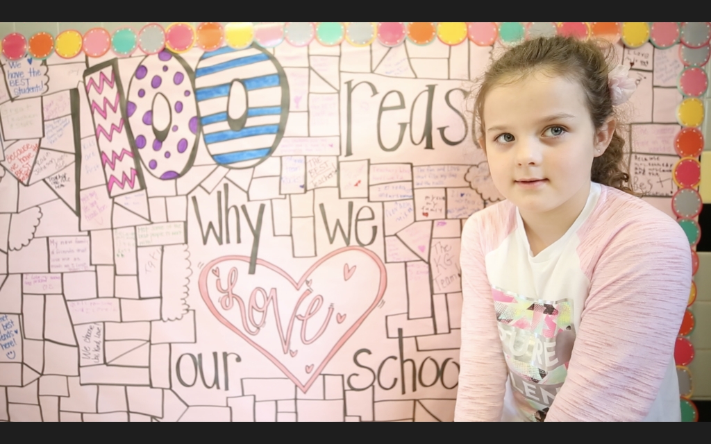 """A QLE students poses by a sign which reads, """"100 Reasons I Love School."""""""
