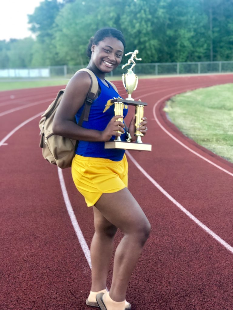Heavin poses with the district track trophy.