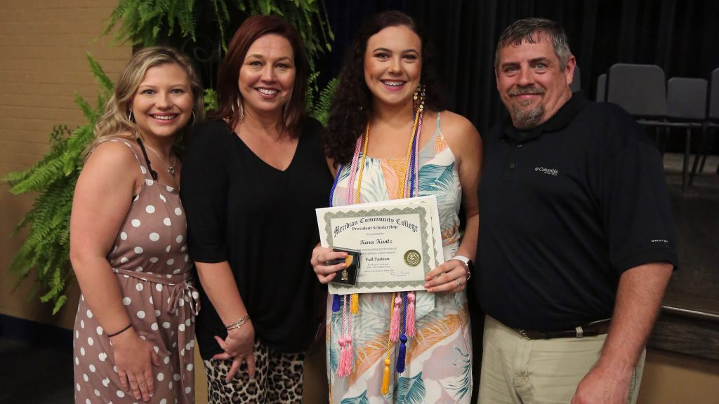 Kara Beth poses with her family on QHS Awards night.