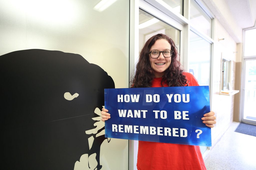 "Kara Beth poses for a photo with a sign which reads, ""How do you want to be remembered?"""