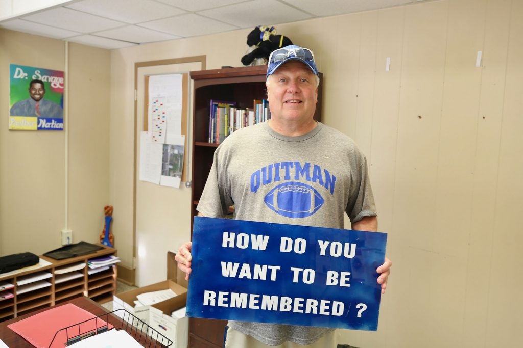 "Coach Russell holds up a sign which reads, ""How do you want to be remembered?"""