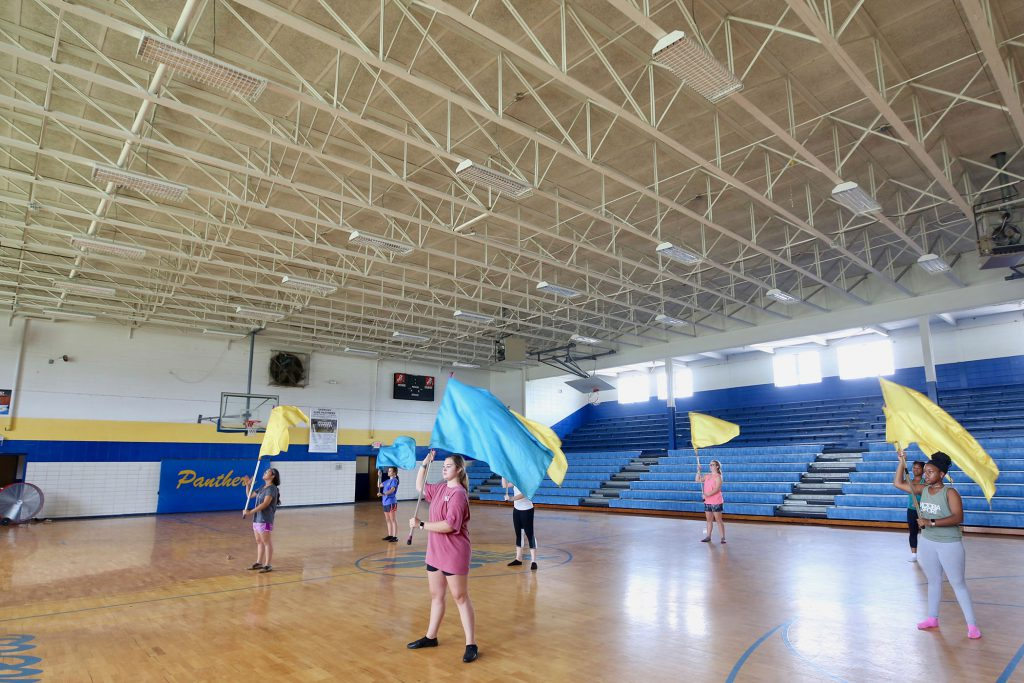 The Big Blue Crew Color Guard practices in the QHS gym.