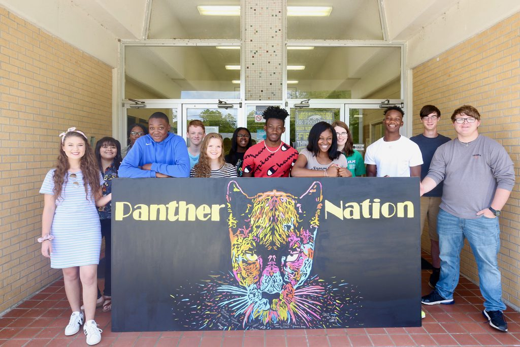 "QHS students pose behind a sign which reads, ""Panther Nation""."