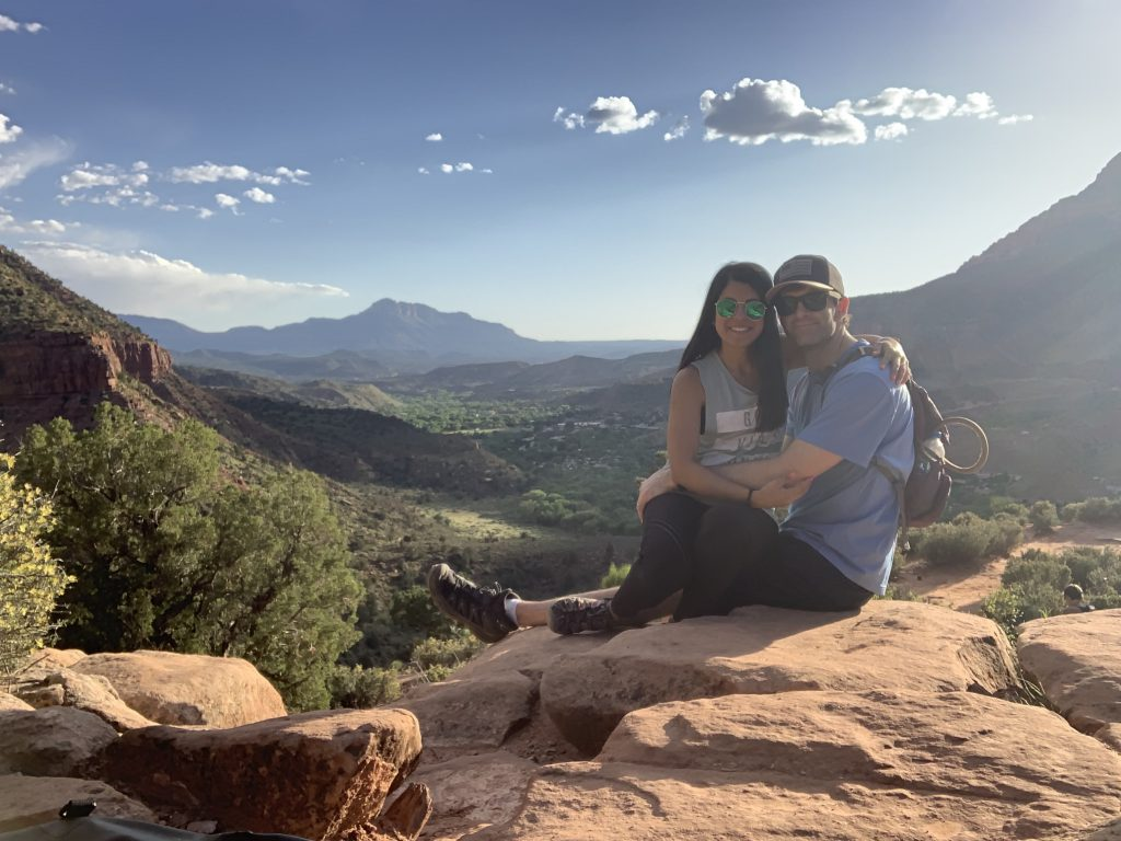 Slater and his wife pose on top of a mountain.